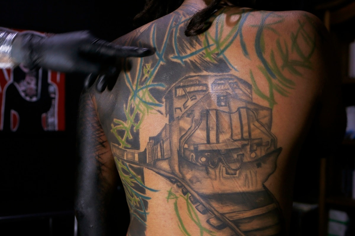 A tattoo artist known as Enrique inks the image of the train known as
