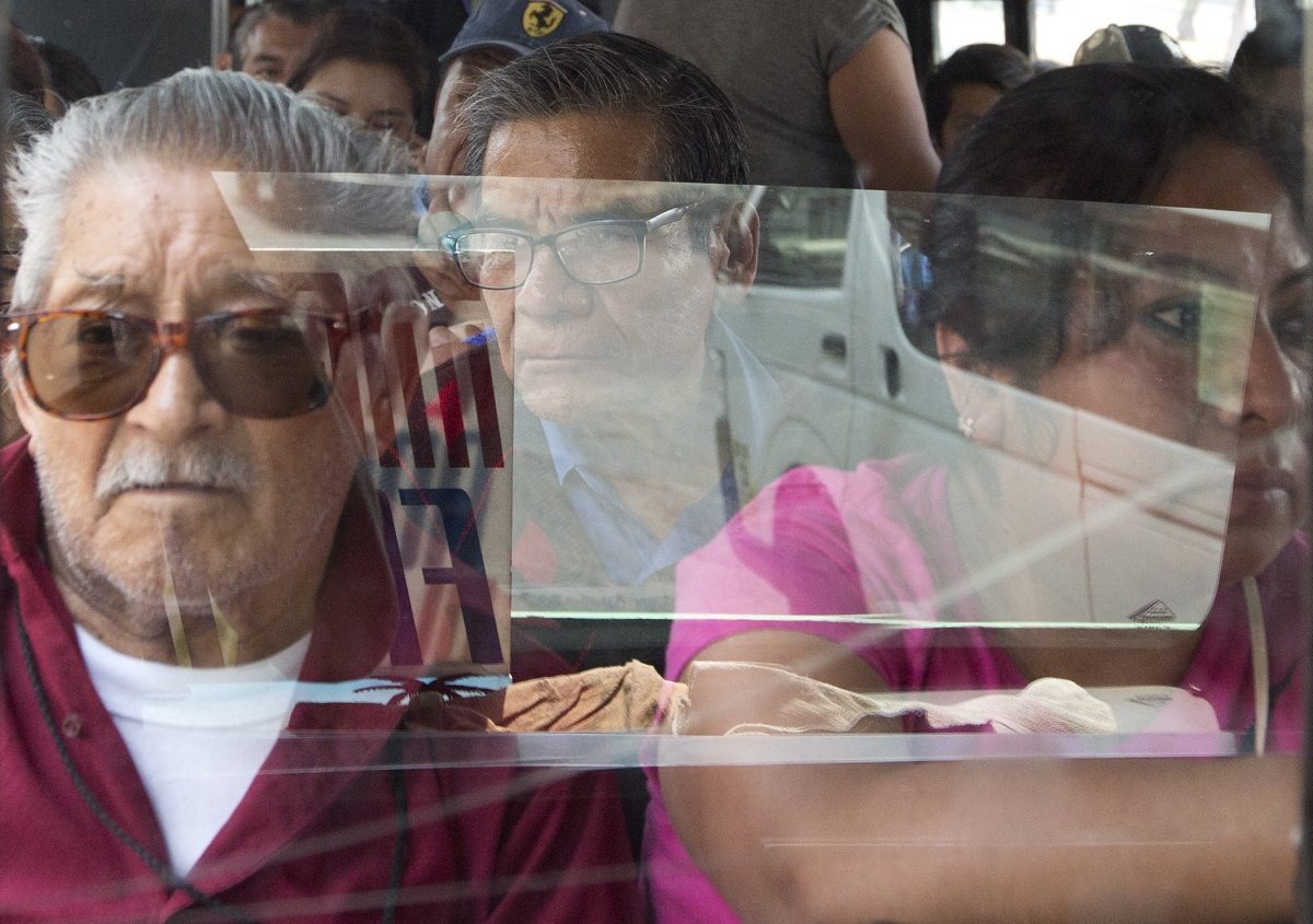 Passengers ride a public bus through the Iztapalapa borough of Mexico City. Vicious armed robberies have gotten so common aboard buses in Mexico City that commuters have come up with a clever if disheartening solution: Many are buying fake cellphones, to hand over to thieves instead of their real smartphones. (AP Photo/Rebecca Blackwell)