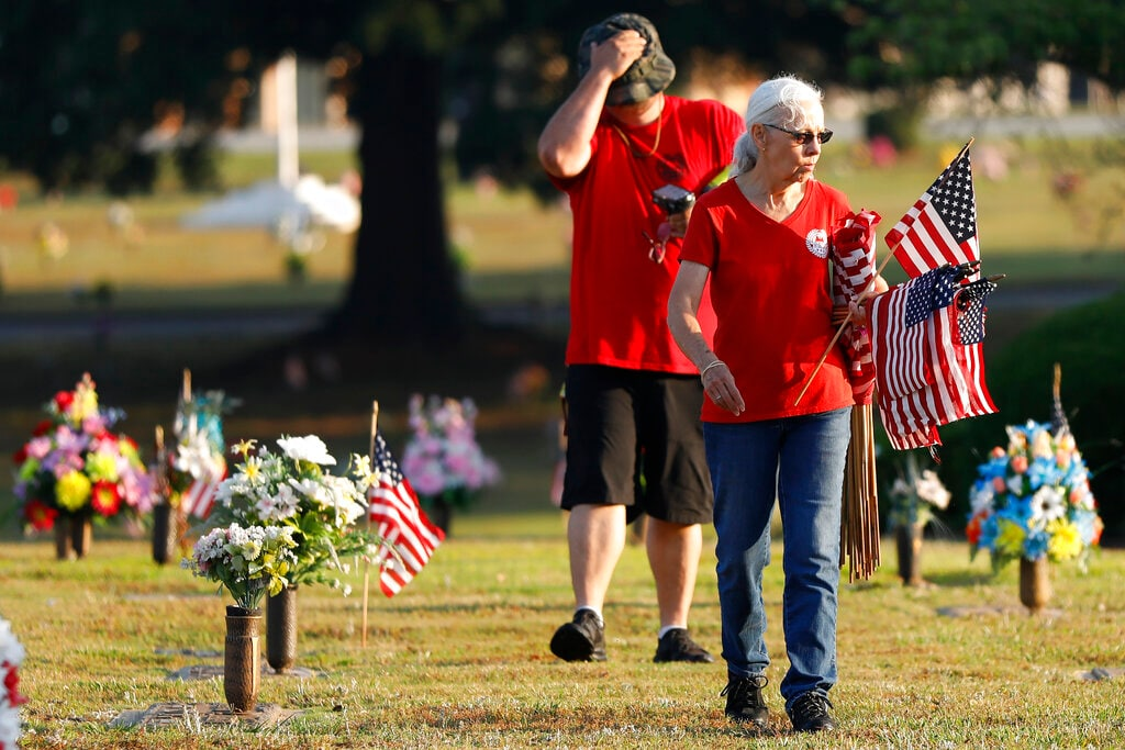 Amvets members from Post 12 in Winder and Post 10 in Athens gathered to place 1,500 flags on the graves of veterans at Evergreen Memorial Park in Athens, Ga., on Saturday, May 25, 2019. It was the third year in a row the group placed flags in observance of Memorial Day weekend. [Joshua L. Jones/Athens Banner-Herald via AP)