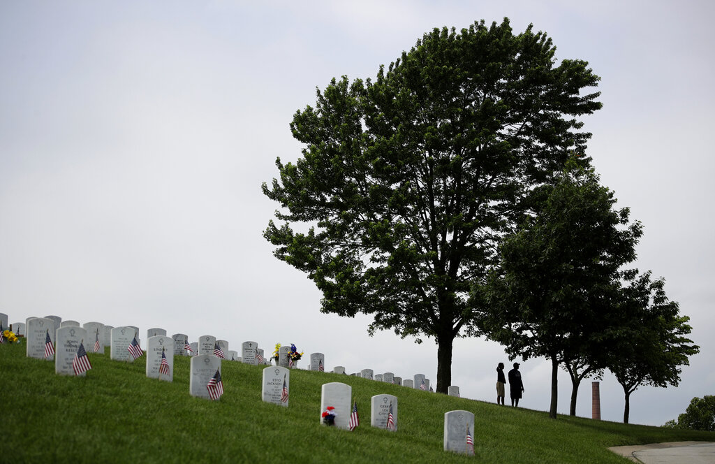 A couple pauses under a shade tree while visiting graves on Memorial Day at Leavenworth National Cemetery Monday, May 27, 2019, in Leavenworth, Kan. (AP Photo/Charlie Riedel)