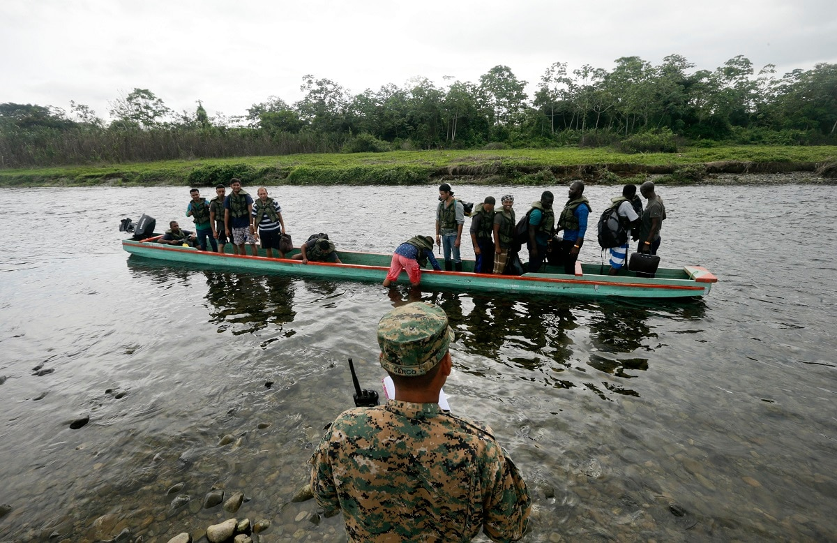 A police officer count migrants in a boat that will navigate the Tuquesa river on their way to Peñitas, in Bajo Chiquito, Darien province, Panama. According to border police, at least a dozen migrants, likely more, have been killed recently by fast-rising rivers elsewhere in Darien. (AP Photo/Arnulfo Franco)