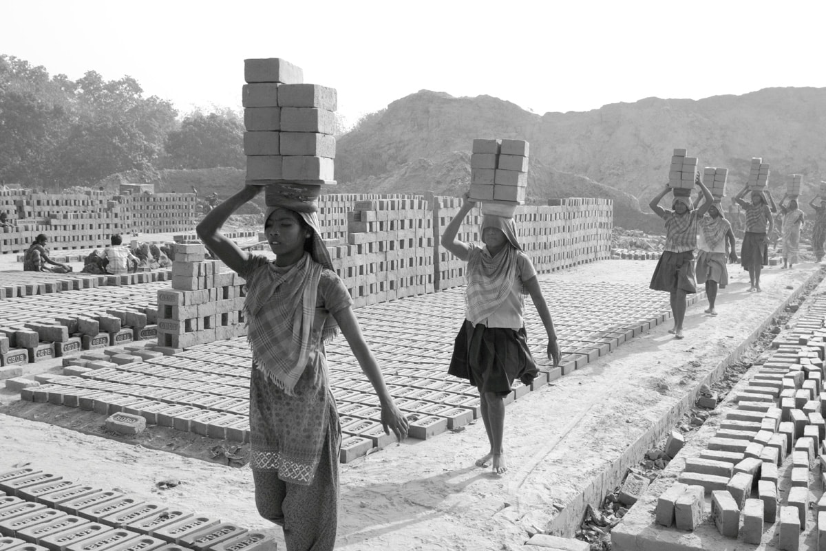 Women carry bricks while working in a brick kiln. Labour Day is celebrated on May 1 every year to commemorate the accomplishments of workers.