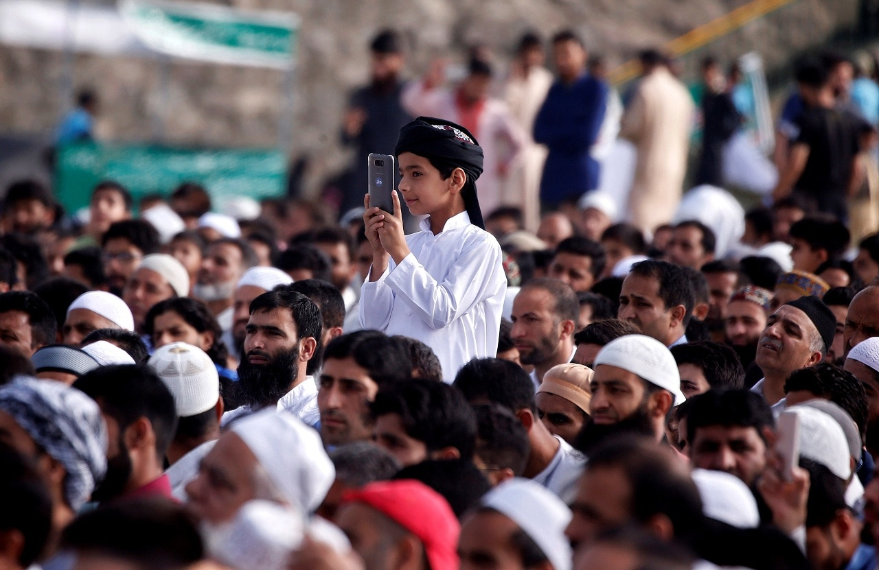A boy takes a picture with his mobile phone during Eid al-Fitr prayers marking the end of the holy fasting month Ramadan, in Srinagar, on June 16, 2018. (Reuters)