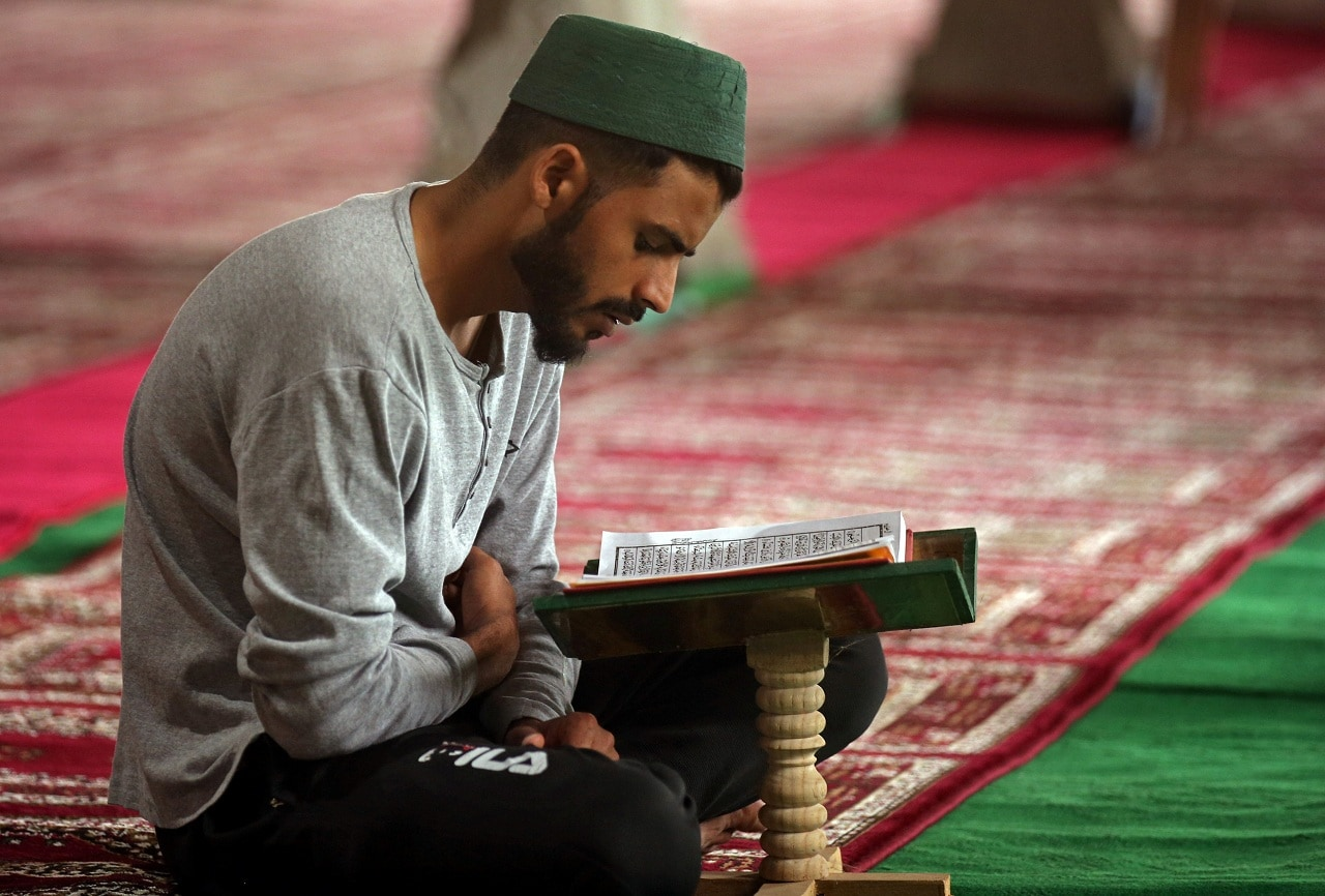 A man reads the Quran inside a mosque in Srinagar on May 9. (Reuters)