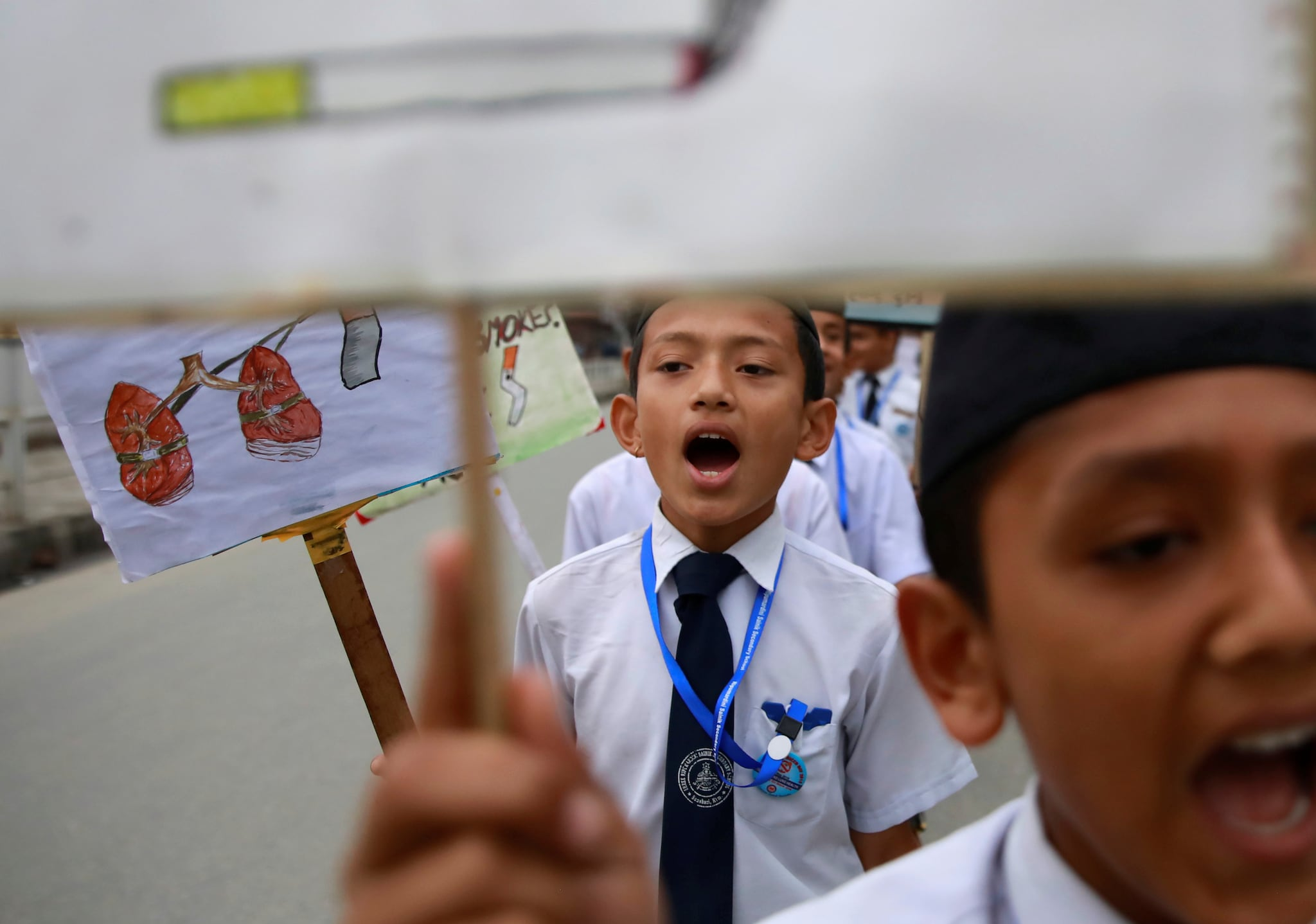 A teacher puts a badge on her student as they take part in a rally during the World No Tobacco Day in Kathmandu, Nepal May 31, 2019. REUTERS/Navesh Chitrakar