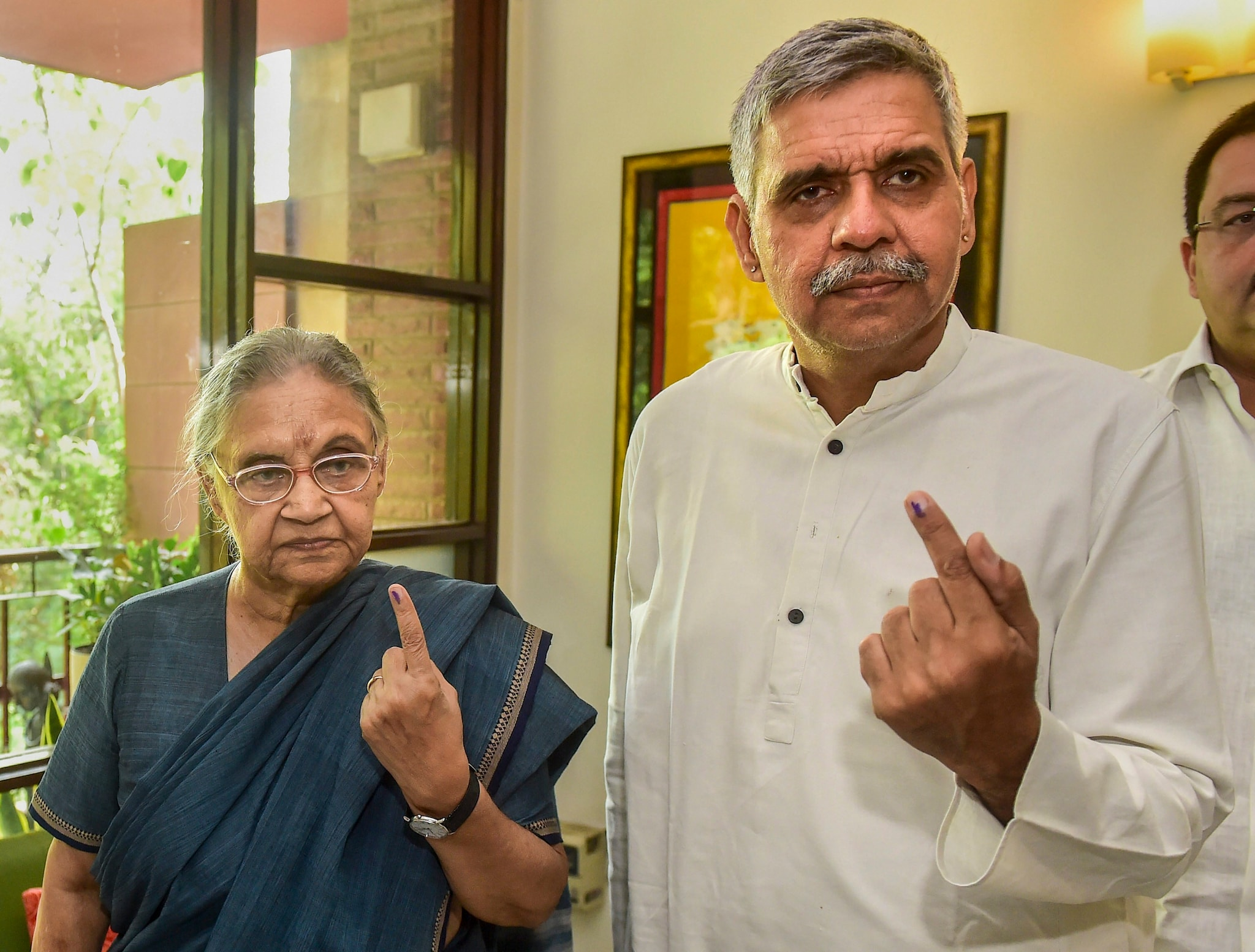 The Congress party's North East Delhi candidate Sheila Dikshit and her son Sandeep Dikshit show their inked fingers.