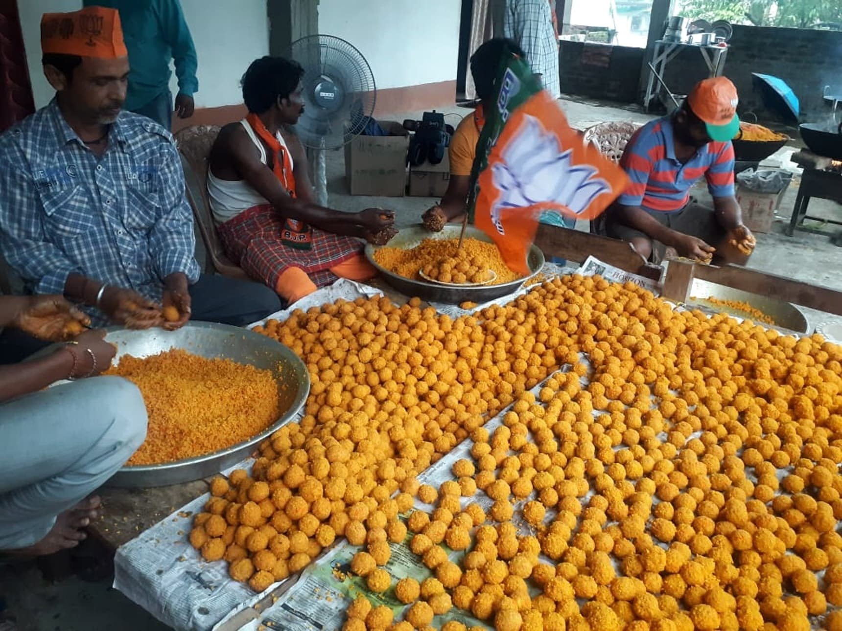 Dibrugarh: Workers wearing BJP caps busy preparing laddus -sweets- at a workshop on the eve of counting for 2019 Lok Sabha polls in Dibrugarh, Assam on May 22, 2019. (Photo: IANS)