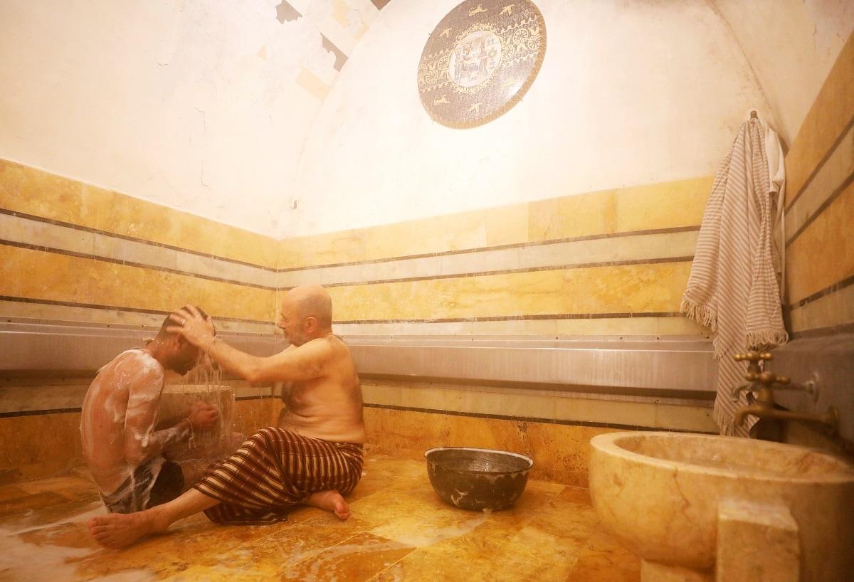 A bathhouse attendant washes a customer in Aleppo's Bab al-Ahmar public bathhouse. REUTERS/Omar Sanadiki