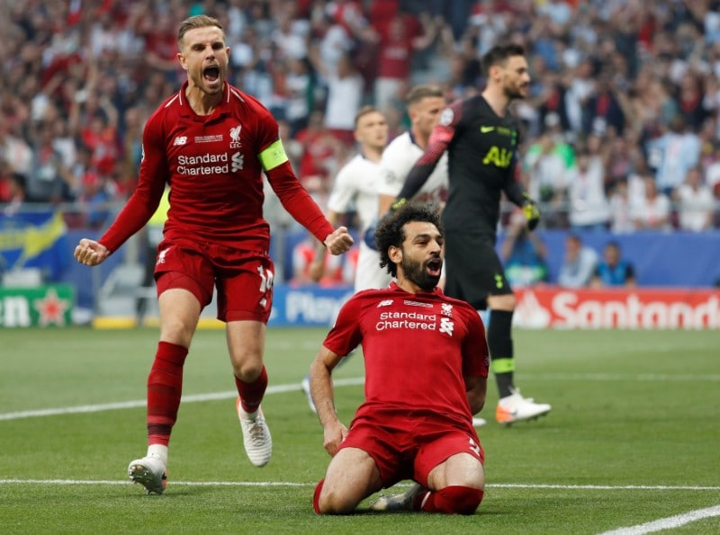 Salah celebrates putting his team in front from the penalty spot with Jordan Henderson. (Reuters)