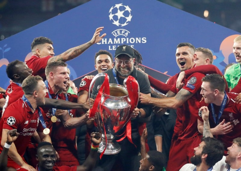 Liverpool boss Klopp celebrates with the trophy and his players. (Reuters)