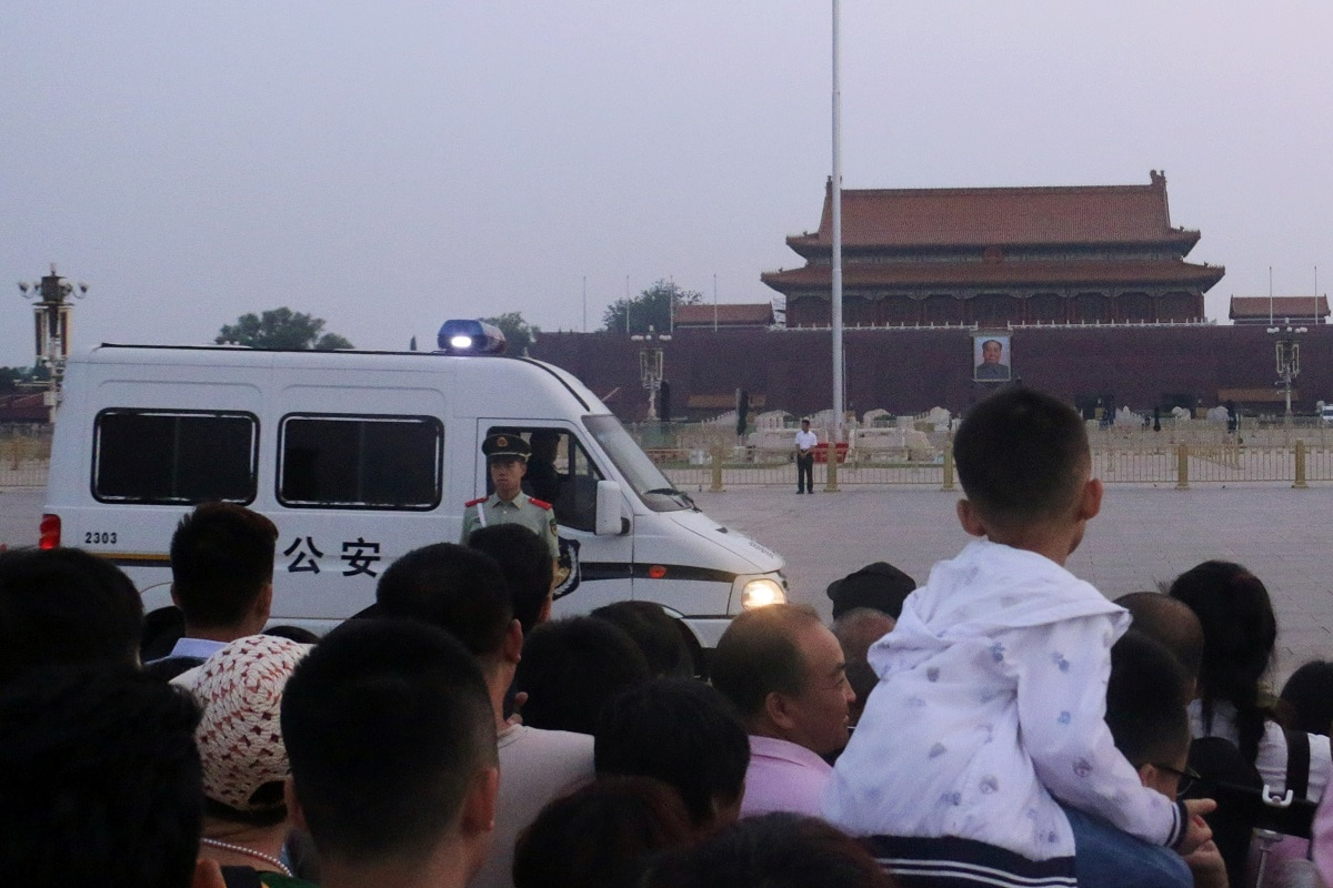 A paramilitary police officer stands guard in front of a police vehicle as people wait for the flag-raising ceremony held at Tiananmen Square. The anniversary of the Tiananmen crackdown, when Beijing sent troops and tanks to quell pro-democracy activists, is not spoken of openly in China and will not be formally marked by the government, which has ramped up censorship. REUTERS/Stringer