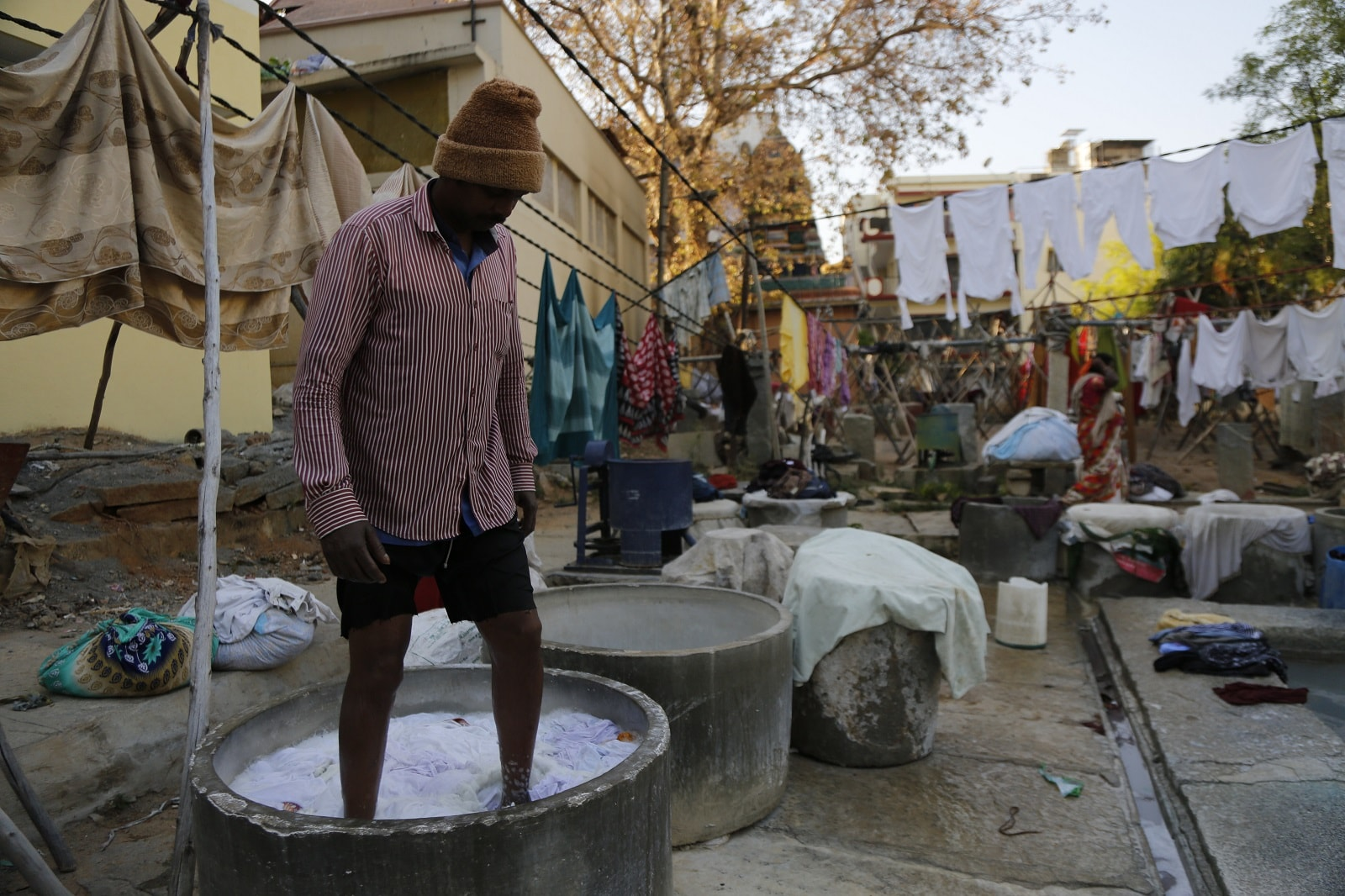 A washerman soaks clothes in detergent water at an open-air laundromat in Bangalore,  on March 13, 2019. Thomson Reuters Foundation/Rajan Zaveri