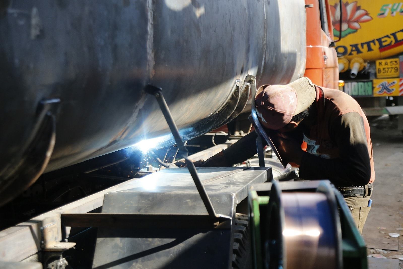 A worker welds together a water tanker at a local manufacturing workshop in Bangalore, on March 12, 2019. Thomson Reuters Foundation/Rajan Zaveri