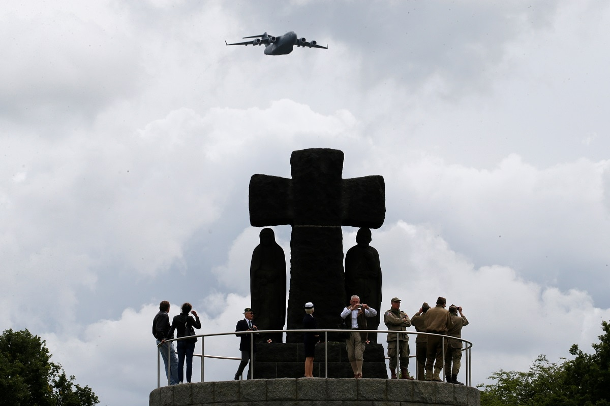 A plane flies over a cross of La Cambe German war cemetery during a remembrance ceremony in La Cambe in Normandy as France prepares to commemorate the 75th anniversary of the D-Day. REUTERS/Pascal Rossignol