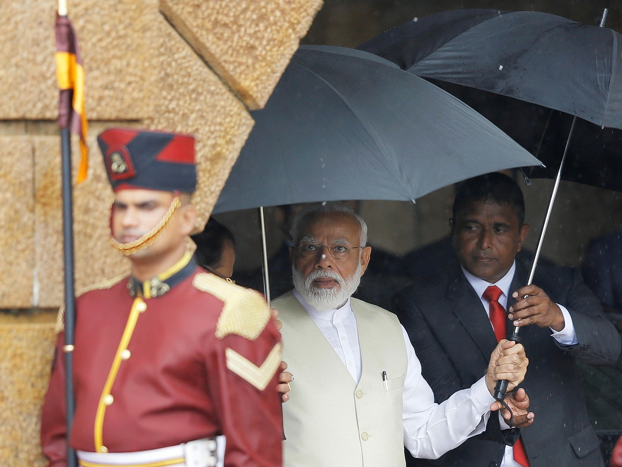 India's Prime Minister Narendra Modi holds an umbrella during his welcome ceremony at the Presidential Secretariat in Colombo, Sri Lanka, June 9, 2019. REUTERS/ Dinuka Liyanawatte