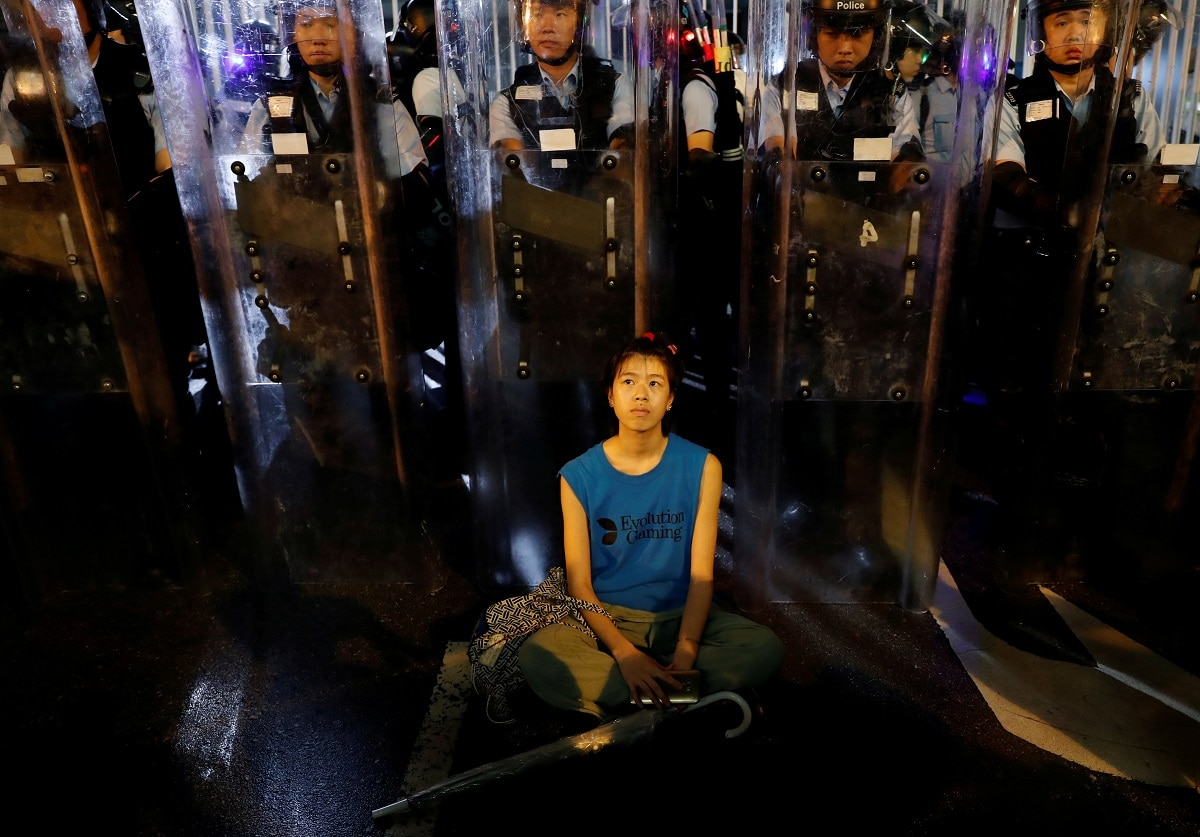 A demonstrator sits down in front of riot police during a demonstration to demand authorities scrap a proposed extradition bill. REUTERS/Tyrone Siu