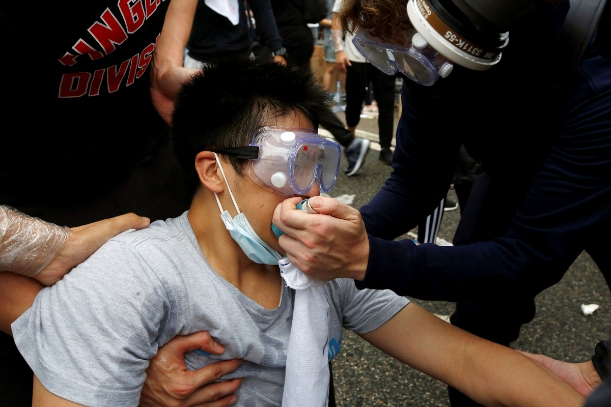 Protesters help a man during a demonstration against a proposed extradition bill where tear gas was fired, in Hong Kong. REUTERS/James Pomfret