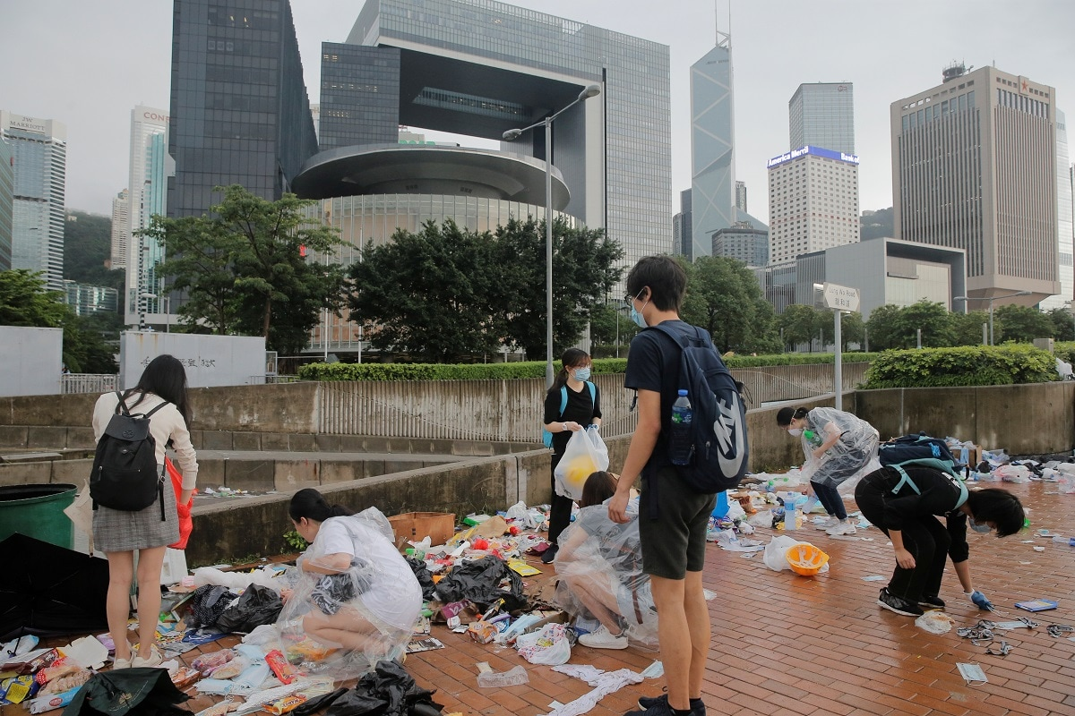 People clear rubbish outside the Legislative Council building after violent clashes during a protest against a proposed extradition bill with China in Hong Kong. Opponents, including leading lawyers and rights groups, say China's justice system is marked by torture and forced confessions, arbitrary detention and poor access to lawyers. REUTERS/Thomas Peter