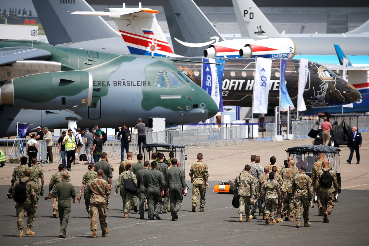 Soldiers walk past aircrafts on static display, at the eve of the opening of the 53rd International Paris Air Show at Le Bourget Airport. REUTERS/Pascal Rossignol