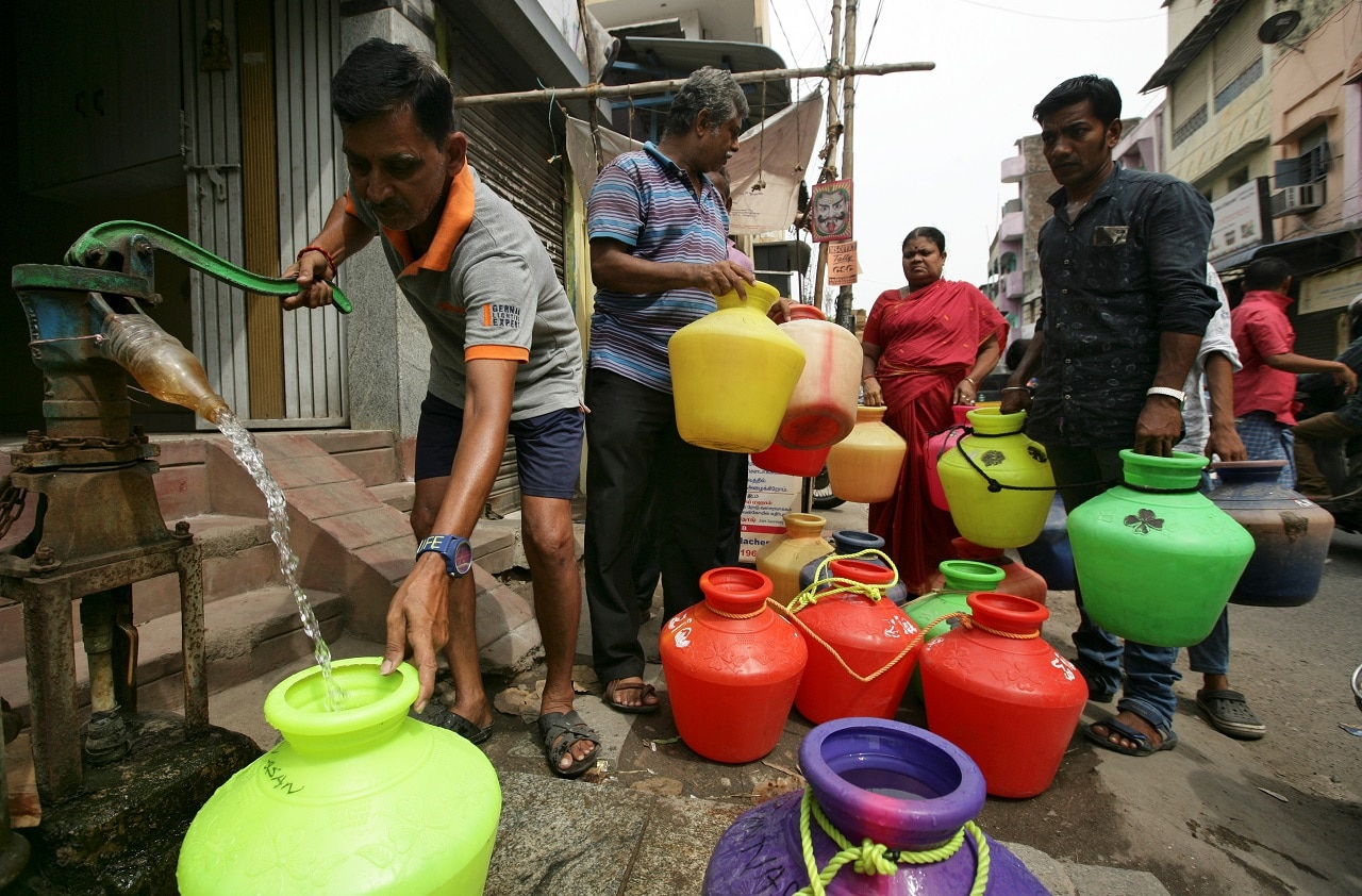 A man uses a hand-pump to fill up a container with drinking water as others wait in a queue on a street in Chennai, June 17, 2019. REUTERS/ P. Ravikumar