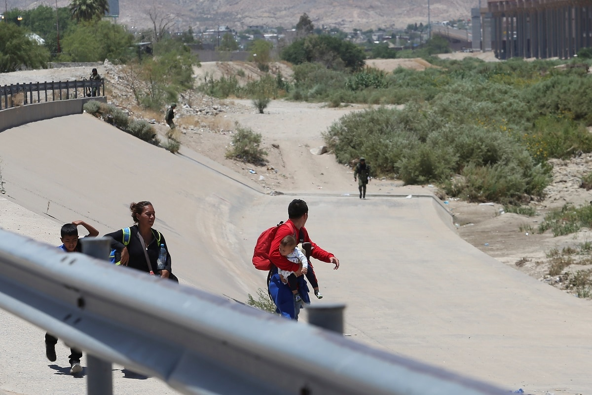 Migrants move away from members of the Mexican National Guard before crossing illegally into Texas. REUTERS/Carlos Sanchez Colunga NO RESALES. NO ARCHIVES.