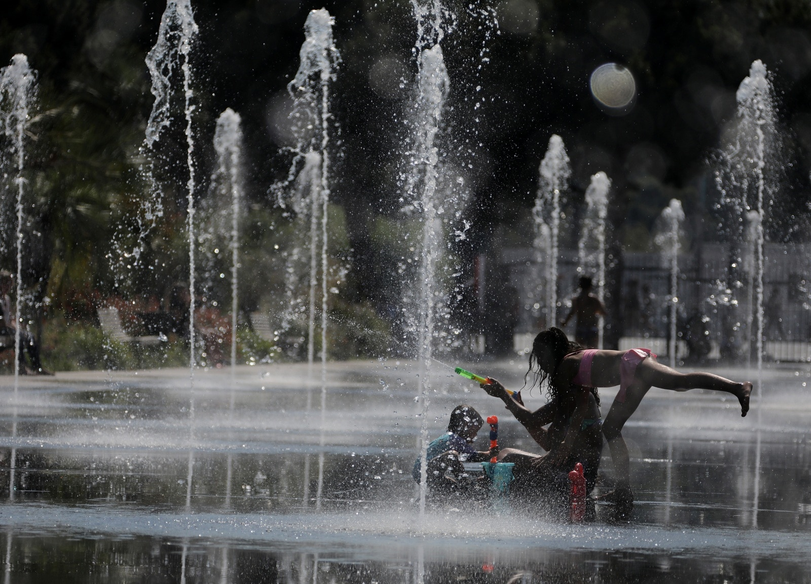 People cool off in a fountain in Nice as a heatwave hits much of the country, France, June 27, 2019. REUTERS/Eric Gaillard