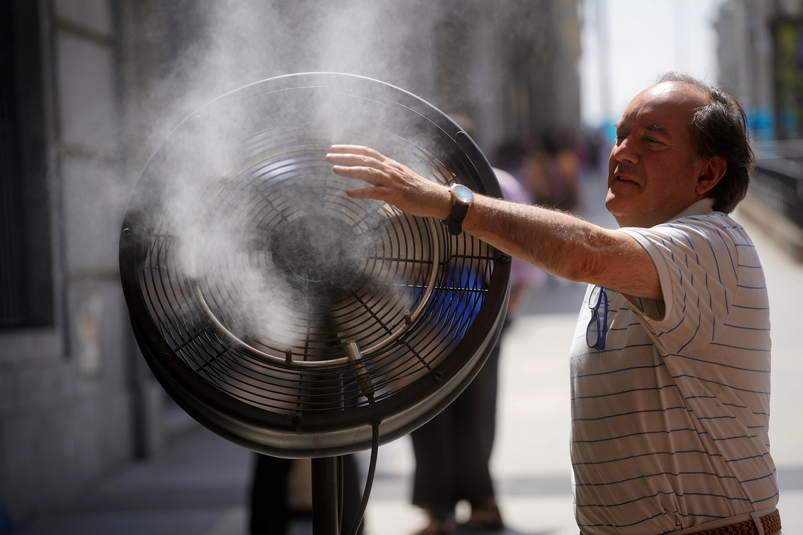 A man tries to cool himself with a fan in central Madrid, Spain, June 27, 2019. REUTERS/Juan Medina
