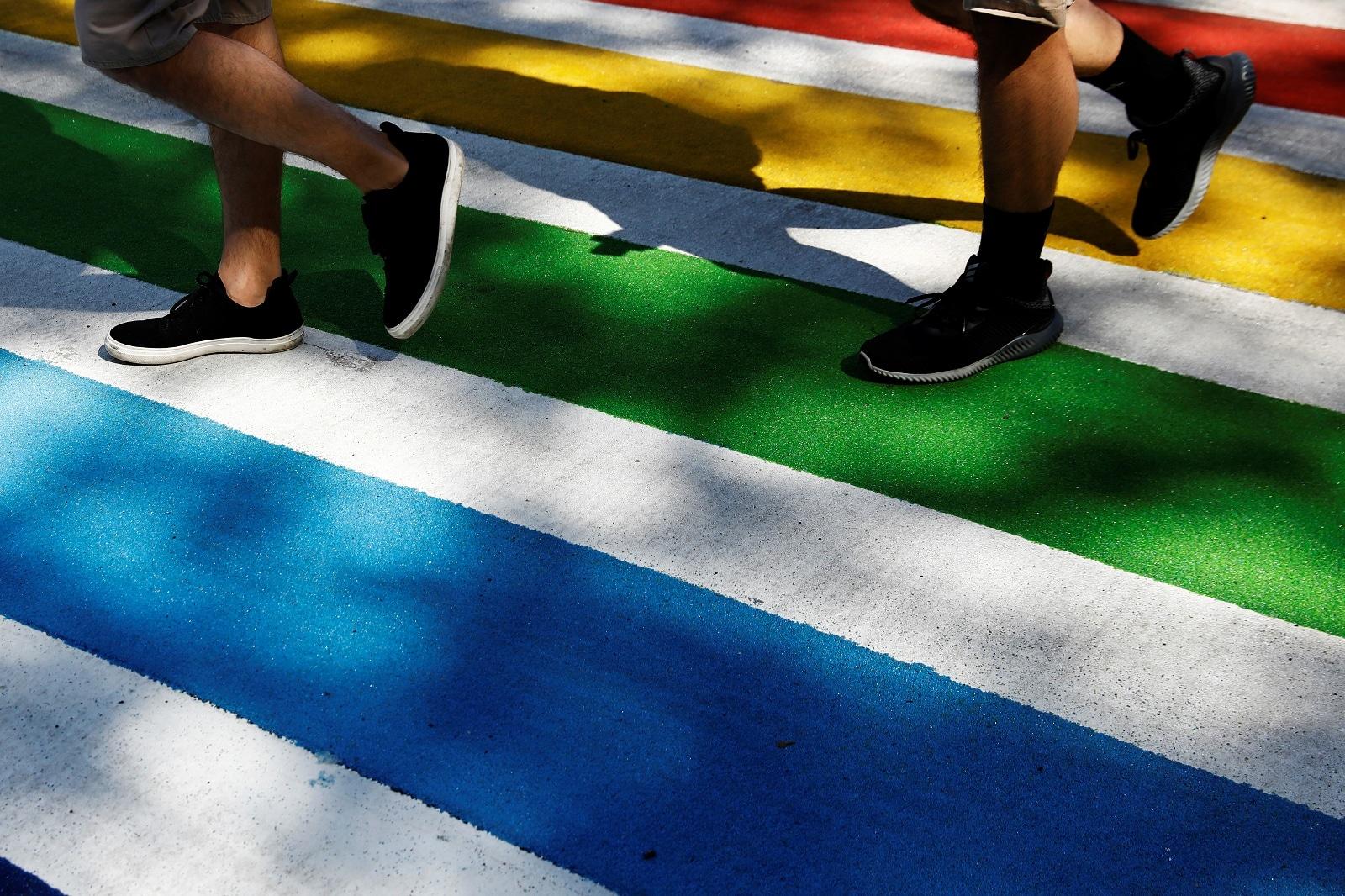 Men walk across a rainbow coloured sidewalk at Christopher street near the Stonewall Inn in New York, US, June 27, 2019. REUTERS/Shannon Stapleton