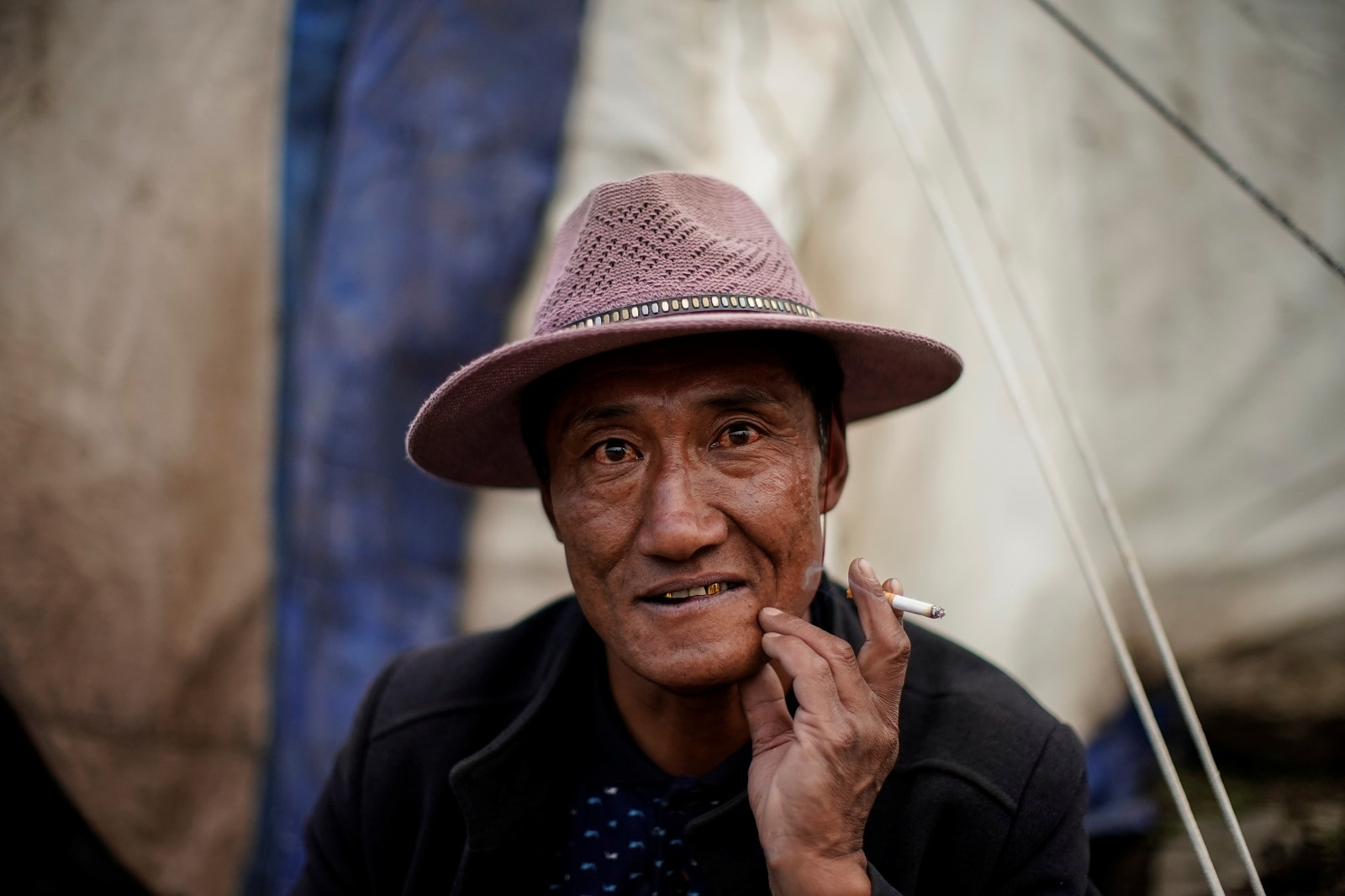 A Tibetan cordyceps picker smokes a cigarette at a base camp on a mountain in the Amne Machin range in China's western Qinghai province, June 7, 2019. REUTERS/Aly Song