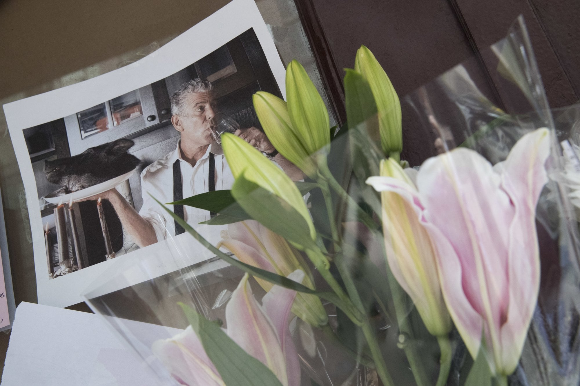 Flowers and a photo of Anthony Bourdain are seen at a make shift memorial outside the building that once housed Le Halles restaurant on Park Avenue, Friday, June 8, 2018, in New York. Bourdain, the celebrity chef and citizen of the world who inspired millions to share his delight in food and the bonds it created, was found dead Friday in his hotel room in France while working on his CNN series on culinary traditions. He was 61. (AP Photo/Mary Altaffer)
