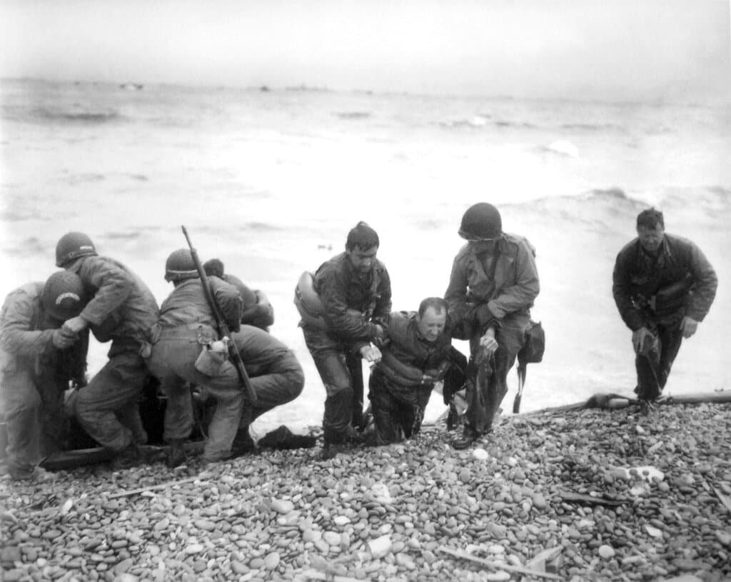 Members of an American landing unit help their comrades ashore during the Normandy invasion. The men reached the zone code-named Utah Beach, near Sainte- Mere-Eglise, on a life raft after their landing craft was hit and sunk by German coastal defenses. June 6, 1944. (Louis Weintraub/Pool Photo via AP, File)