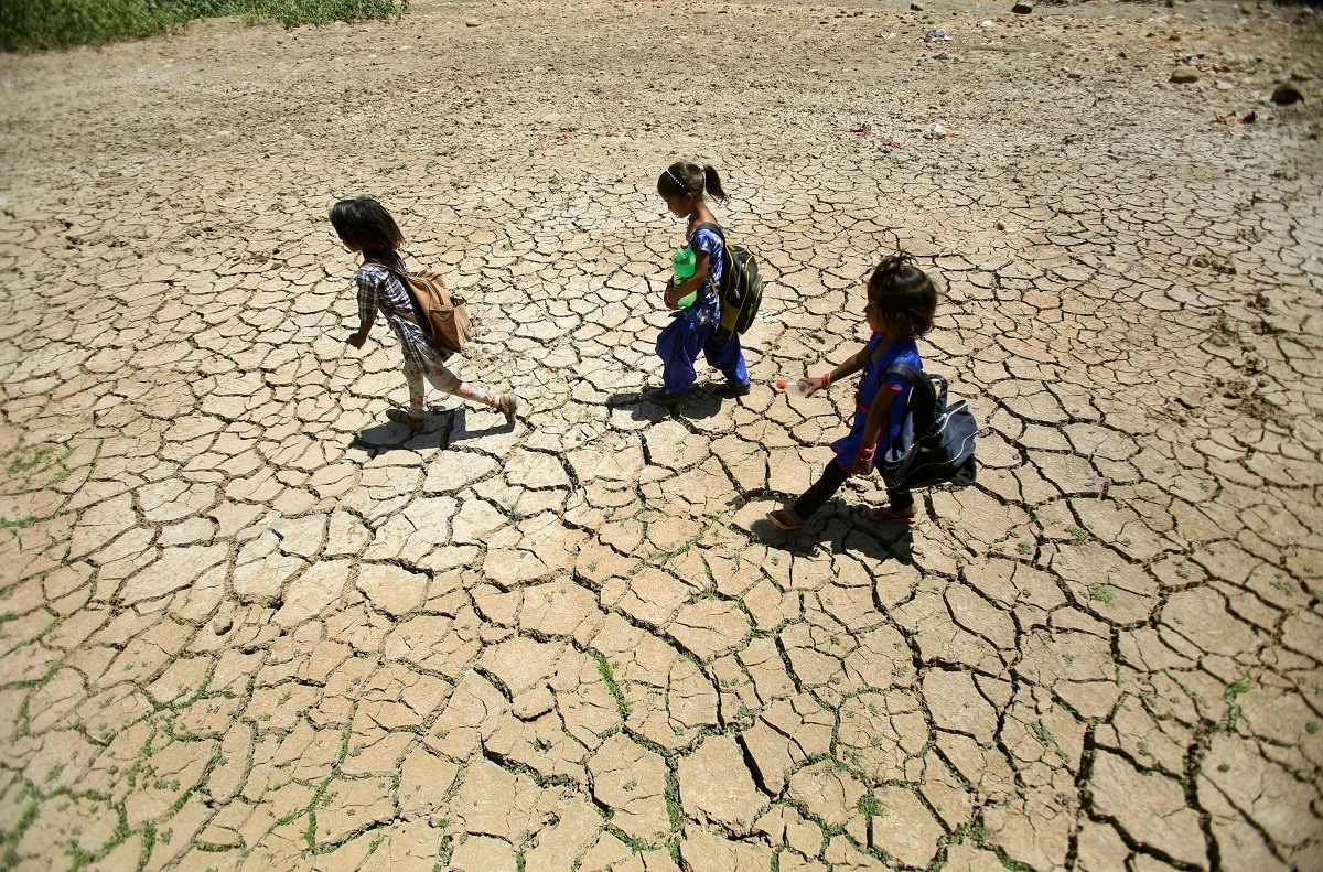 Children returning from school walk through a dried pond on a hot summer day on the outskirts of Jammu.  (AP Photo/Channi Anand, File)