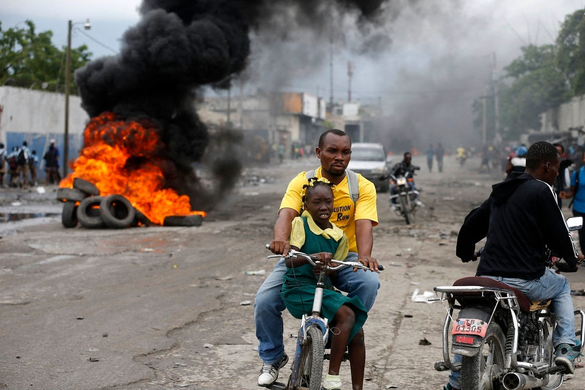 A father carries his daughter on a bicycle past a burning barricade during a protest against the ratification of interim Prime Minister Jean Michel Lapin, in Port-au-Prince, Haiti. ( AP Photo/Dieu Nalio Chery)