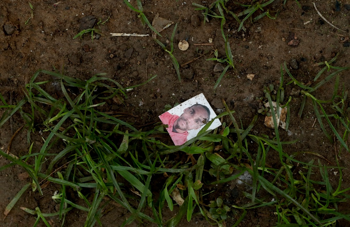 The mugshot of an unknown migrant lays on the ground in Bajo Chiquito, Darien province, Panama. As migrants surge on the country's borders, Panamanian President Juan Carlos Varela acknowledged the difficulty of dealing with problem, which has left authorities scrambling to impose order. (AP Photo/Arnulfo Franco)