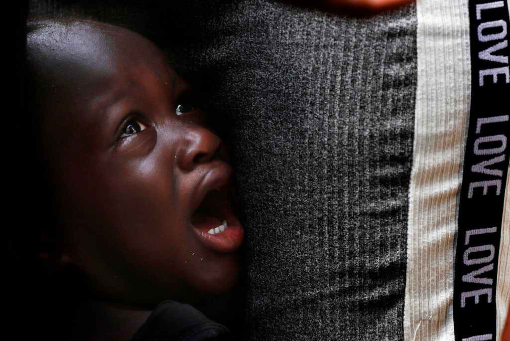 A Haitian migrant youth cries next to his father as they wait in line at an immigration center in Tapachula, Chiapas state, Mexico, Tuesday, May 28, 2019. The Mexican government is trying to encourage more migrants to regularize their status and stay in the south, but for most the United States remains the goal. (AP Photo/Marco Ugarte)