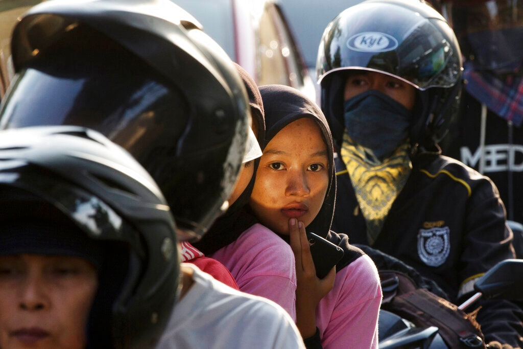 People ride motorcycles in Bekasi on the outskirts of Jakarta, Indonesia, Thursday, May 30, 2019. The mass exodus out of Jakarta and other major cities in the world's most populous Muslim country is underway as millions are heading home to their villages to celebrate Eid al-Fitr holiday that marks the end of the holy fasting month of Ramadan. (AP Photo/Achmad Ibrahim)