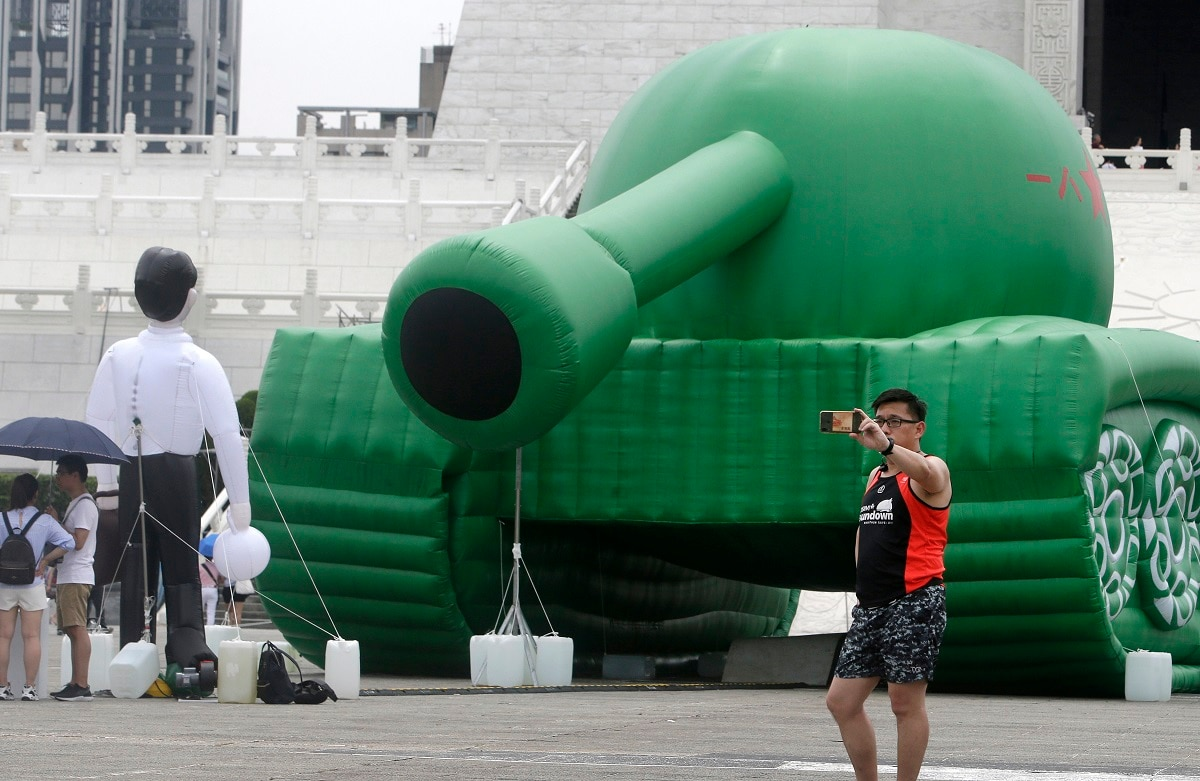 A Taiwanese man takes a selfie with an inflatable tank man at the Liberty Square of Chiang Kai-shek Memorial Hall in Taipei, Taiwan. An artist erected the inflatable display in Taiwan's capital to mark an iconic moment in the Tiananmen Square pro-democracy protests. The larger-than-life balloon installation, which stands in front of Taipei's famous hall, portrays a peaceful encounter between a Chinese civilian and the military tanks that contributed to a brutal shutdown of the demonstrations in Beijing on June 4, 1989. (AP Photo/Chiang Ying-ying, File)
