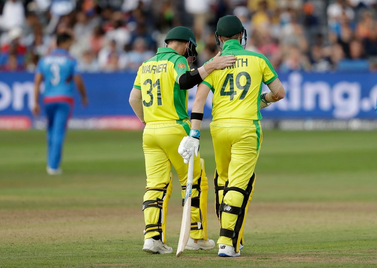 Australia's David Warner, left, pats Australia's Steve Smith on the back as Smith comes in to start their first batting over together during the Cricket World Cup match. Steve Smith and David Warner were back in the Australia lineup for their first official one-day internationals since returning from 12-month bans for their part in a ball-tampering scandal in South Africa last year. (AP Photo/Matt Dunham)
