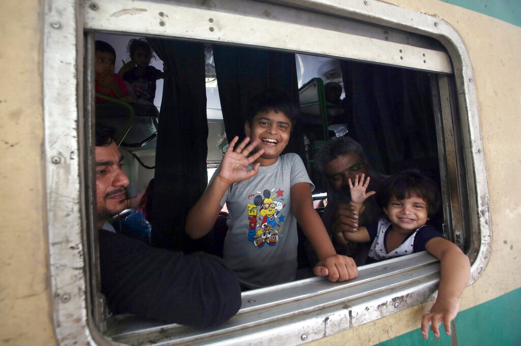 Children wave from a train as they depart for their hometown for the upcoming Eid al-Fitr holidays, at a railway station in Karachi, Pakistan, Sunday, June 2, 2019. (AP Photo/Fareed Khan)