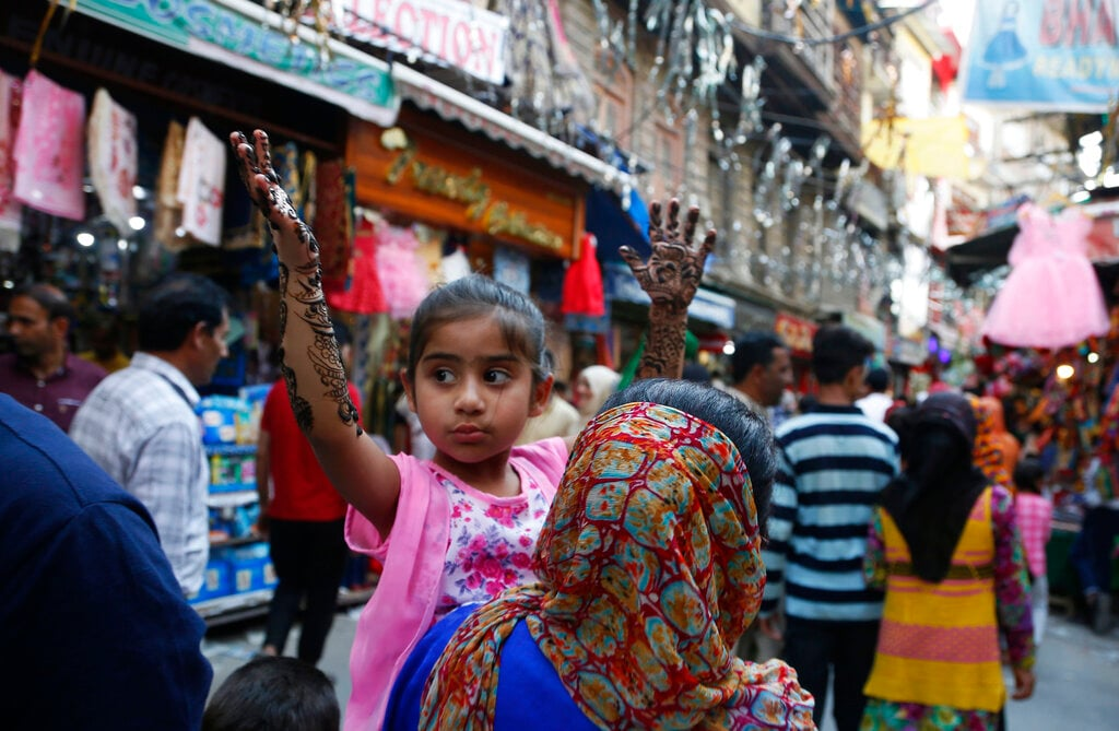 A Kashmiri woman carries a child who holds her hands up to avoid freshly applied henna from getting smudged, at a market ahead of Eid al-Fitr in Srinagar, Kashmir, Sunday, June 2, 2019. (AP Photo/Mukhtar Khan)
