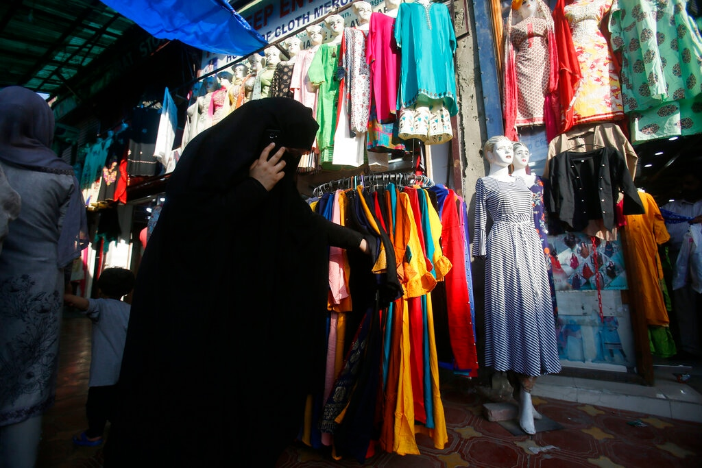 A veiled Kashmiri Muslim woman shops ahead of Eid al-Fitr in Srinagar, Kashmir, Sunday, June 2, 2019. (AP Photo/Mukhtar Khan)