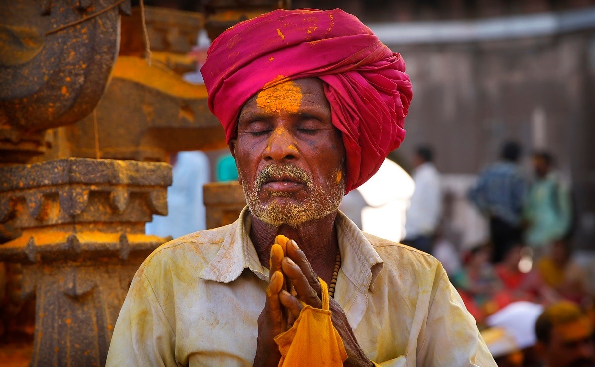 A devotee smeared in the spice turmeric prays during the celebration. (AP Photo/Rafiq Maqbool)