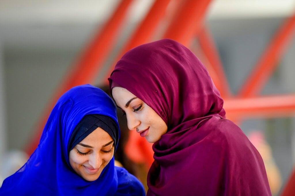 Girls wait for the start of Eid al-Fitr prayers in Bucharest, Romania, Tuesday, June 4, 2019. Members of the Romanian Muslim community gathered for Eid al-Fitr prayers, marking the end of the holy fasting month of Ramadan. (AP Photo/Andreea Alexandru)
