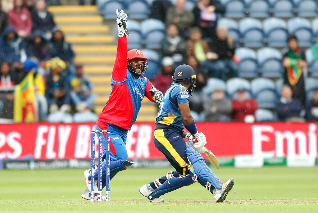 Afghanistan's Mohammad Shahzad claims the catch to dismiss Sri Lanka's Kusal Perera during the Cricket World Cup group stage match against Afghanistan at the Cardiff Stadium, Wales, Tuesday, June 4, 2019. (David Davies/PA via AP)