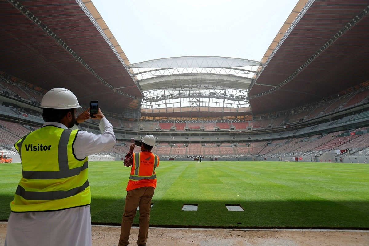 A site engineer and a visitor take photos with their mobile phones during a tour at the Al Bayt stadium in Al Khor, about 50 kilometres (30 miles) north of Doha, Qatar.  (AP Photo/Kamran Jebreili)