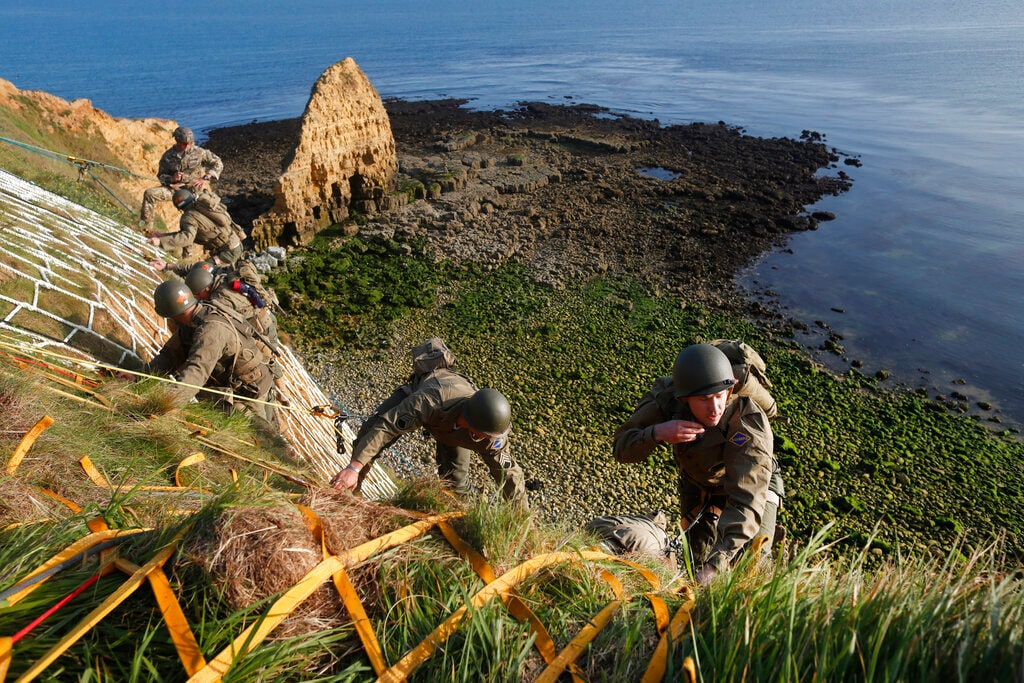 Soldiers from the US 75th Ranger Regiment, in period dress, climb the cliff of Pointe-du-Hoc in Cricqueville-en-Bessin, Normandy, France, Wednesday, June 5, 2019. During the American assault of Omaha and Utah beaches on June 6, 1944, US Army Rangers scaled the 100-foot cliffs to seize German artillery pieces that could have fired on the American landing troops. (AP Photo/Thibault Camus)