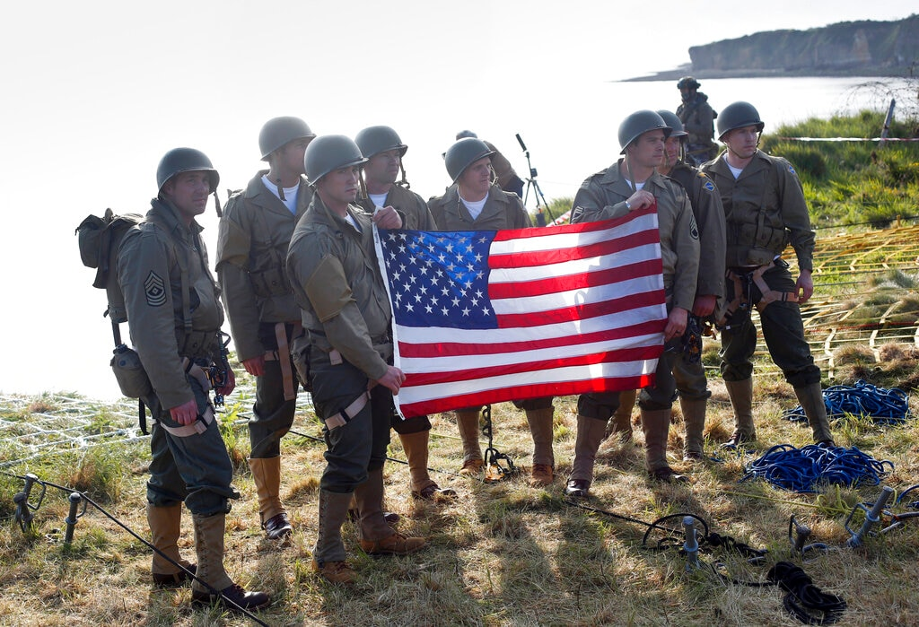 Rangers from the US 75th Ranger Regiment, in period dress, hold the American flag after scaling the cliffs of Pointe-du-Hoc in Cricqueville-en-Bessin, Normandy, France, Wednesday, June 5, 2019. (AP Photo/Thibault Camus)