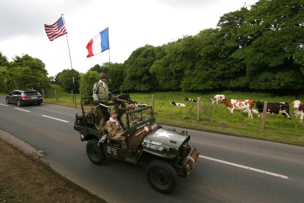 Cows watch WWII enthusiasts driving a jeep in Colleville-Sur-Mer, Normandy, Wednesday, June 5, 2019. (AP Photo/David Vincent)
