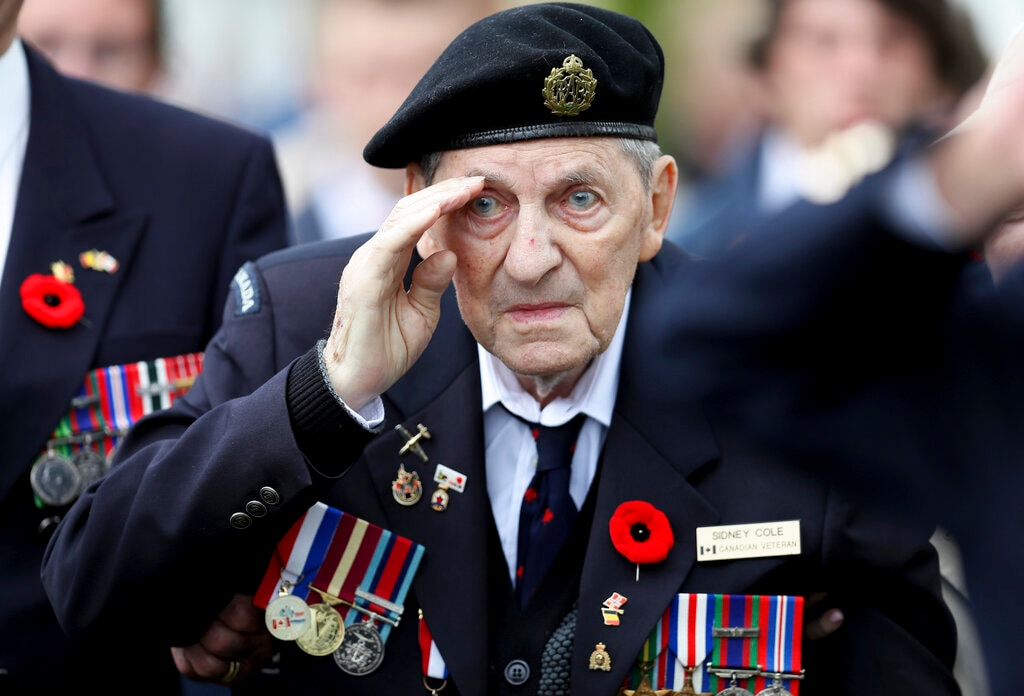 Canadian World War II veteran Sidney Cole salutes as he attends a ceremony at the Beny-sur-Mer Canadian War Cemetery in Reviers, Normandy, France, Wednesday, June 5, 2019. (AP Photo/David Vincent)