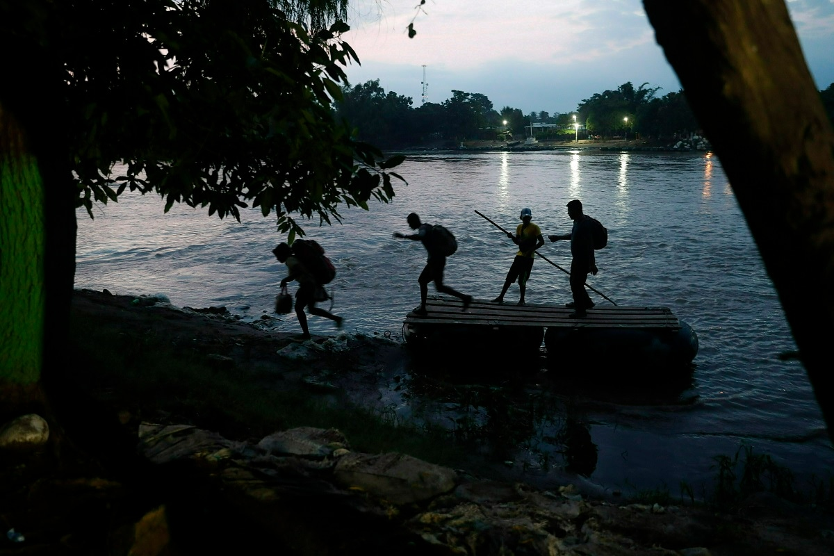Migrants on rafts reach the Mexico shore after crossing the Suchiate River from Guatemala, near Ciudad Hidalgo, Mexico. Hundreds more Central American migrants have crossed into Mexico from Guatemala, and a group of about 1,000 have started walking en mass to the north. (AP Photo/Marco Ugarte)